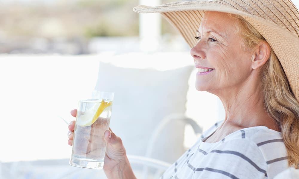 Mature woman drinking lemon water outside in the sun