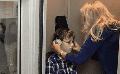 A young boy sitting in a chair ith a blue plaid shirt on getting headphones put on him by a blonde woman in a blue shirt