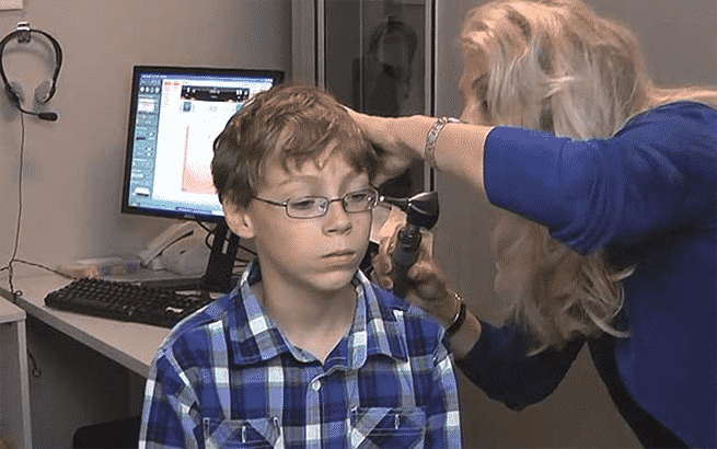 A young boy sitting in a chair with a blue plaid button up getting his ears examined